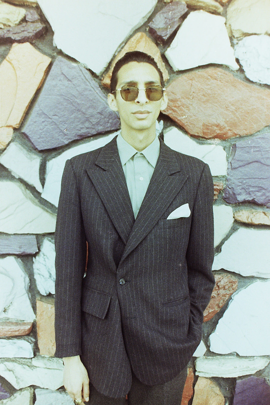 Man in tailored suit wearing GLCO sunglasses
