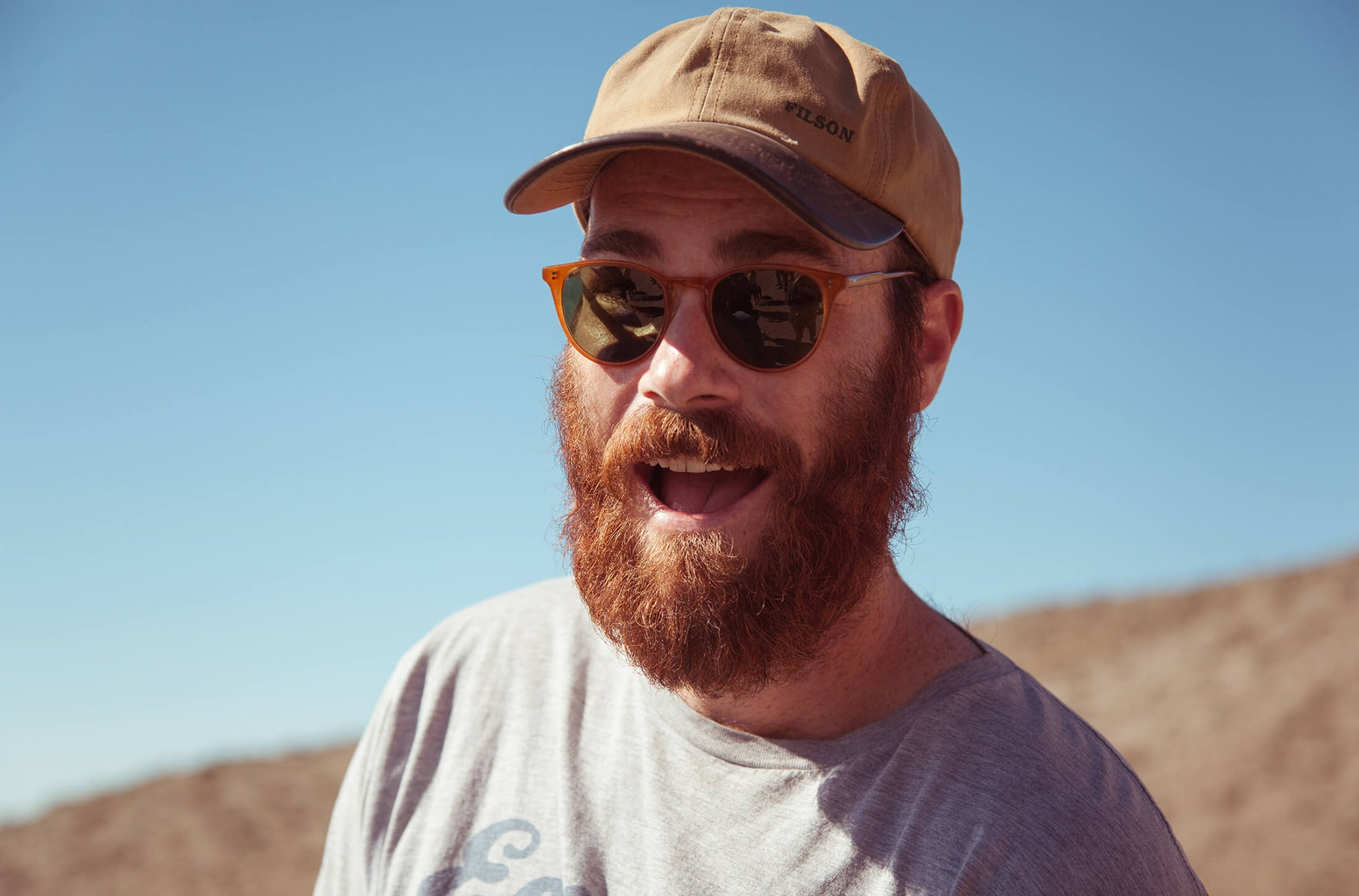 Man wearing Garrett Leight Round Milwood Sunglass in Butterscotch with Pure Green lenses
