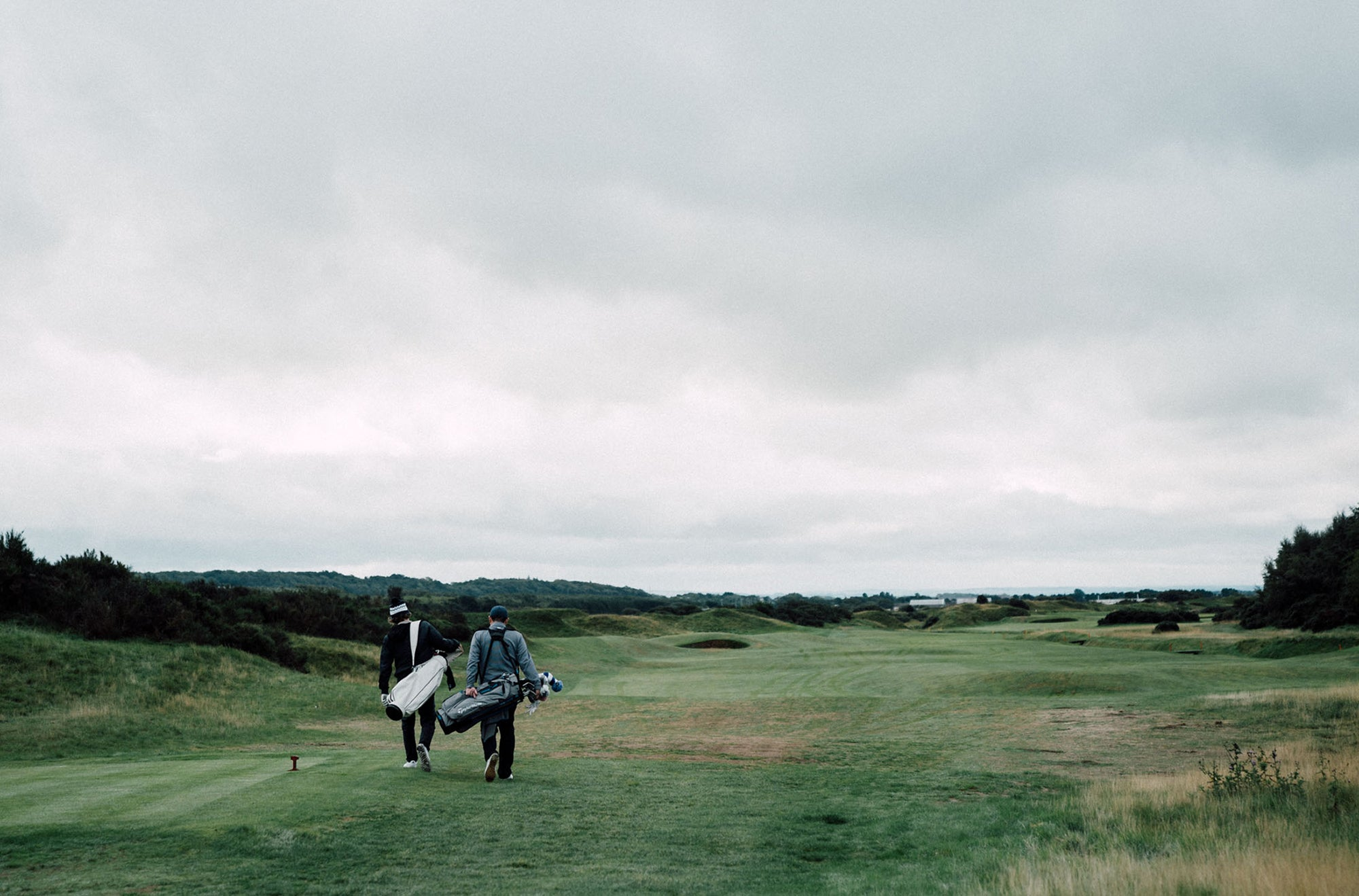 Erik Anders Lang and friend walking on golf course