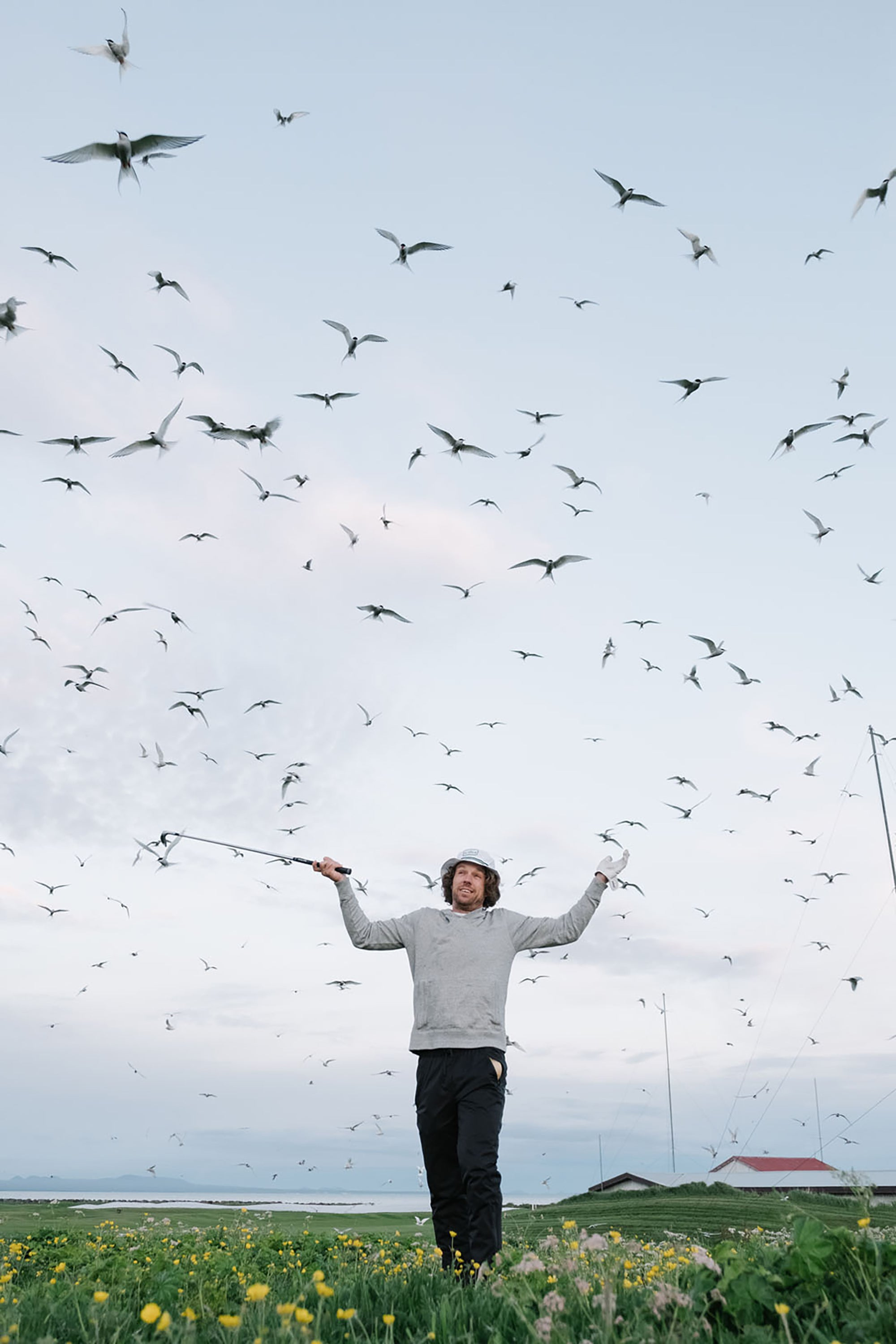 Erik Anders Lang holding up club surrounded by birds flying
