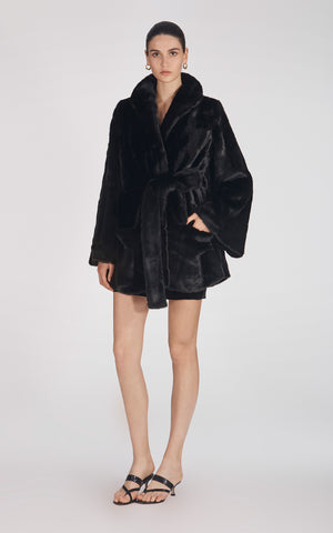 Marei1998's Yoshino Faux Fur Coat In Black Color. Cut In A Slight A-line Silhouette, It Features V-neckline And Bell Sleeves. Matching Tie-up Belt Defines The Waist. As Worn By The Model. Front View. Resort 2020 Collection - Furless Friendship.