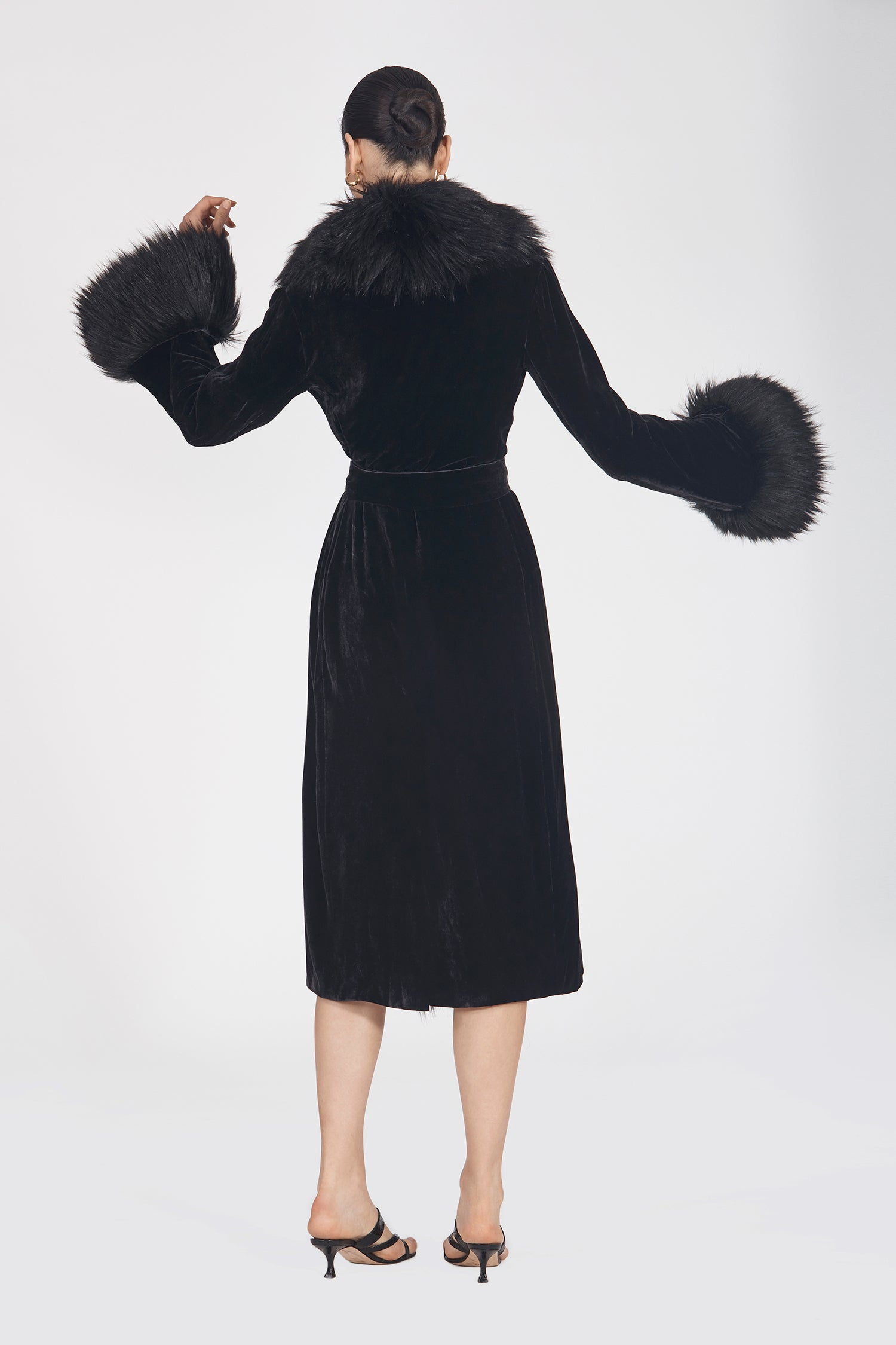 Marei1998's Iconic Powderpuff Long Velvet Coat In Black Color. The Silk Velvet Material, Combined With Faux Fur Trims, Creates A Contemporary Vintage Look. Featuring Wide Lapel Collar And Bell Sleeves, It Is Finished With A Self-Tie Belt To Define The Waist. As Worn By The Model. Back View. Resort 2020 Collection - Furless Friendship.