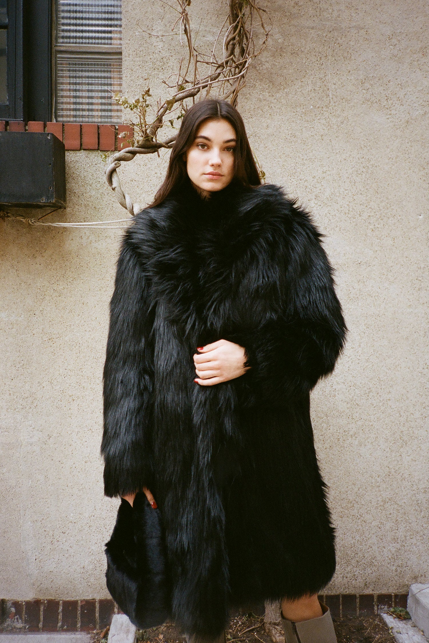 Marei1998's Datura Long Faux Fur Coat In Black Color. Featuring A Slight A-Lined Silhouette, It Is Made From The Fluffiest Long Pile Faux Fur. Back View.