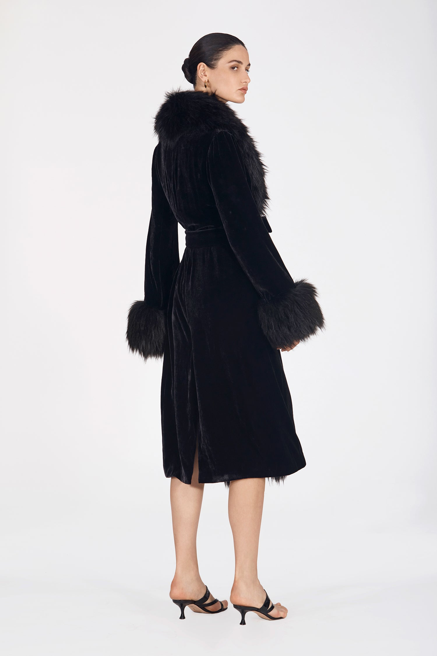 Marei1998's Iconic Powderpuff Long Velvet Coat In Black Color. The Silk Velvet Material, Combined With Faux Fur Trims, Creates A Contemporary Vintage Look. Featuring Wide Lapel Collar And Bell Sleeves, It Is Finished With A Self-Tie Belt To Define The Waist. As Worn By The Model. Side View. Resort 2020 Collection - Furless Friendship.