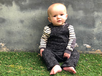 image of baby boy sat on grass against wall wearing grey/cream stripe onesie and black overalls