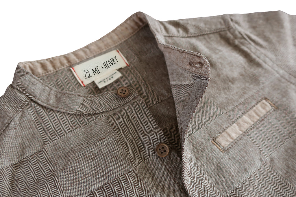 close up image of long sleeved brown plaid shirt with round collar and concealed pocket