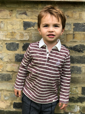 boy standing against brick wall wearing burgundy/cream striped rugby shirt