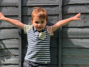 boy standing against grey garden fence with arms outstretched, wearing a multi coloured polo
