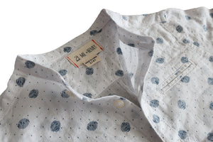 Close up image of white woven round neck long sleeved shirt with navy polka dots all over