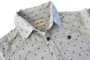 close up image of long sleeved cotton grey woven shirt with navy spots all over