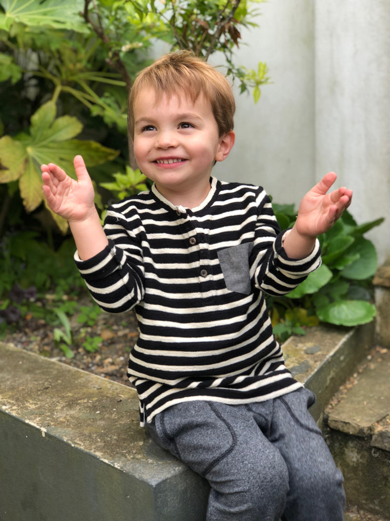 boy sat on garden wall wearing black/cream top smiling with arms outstretched
