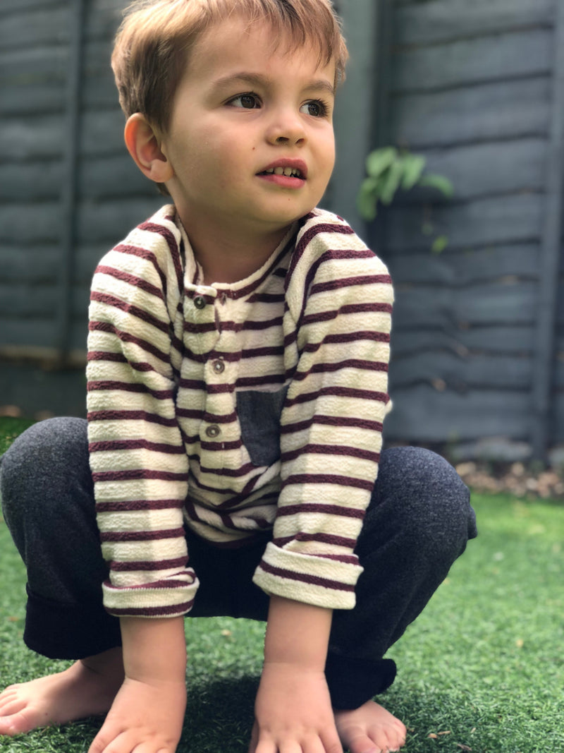boy crouching on floor wearing burgundy/cream striped top