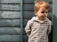 boy standing against grey garden fence wearing beige striped hooded top