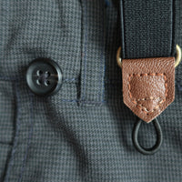 close up image of suspenders showing how they are attached to pants