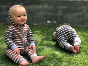 two baby boys sat on grass, one upright , one rolled over on his front, wearing matching striped hooded rompers