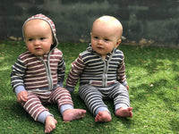 two baby boys sitting on grass wearing hooded stripe romper