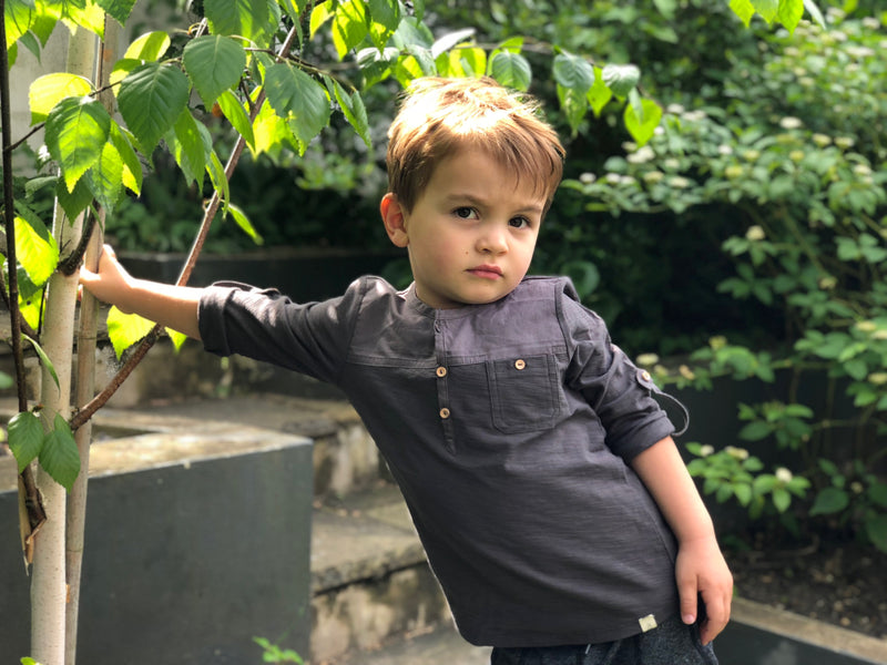 boy leaning against tree wearing black woven and jersey shirt