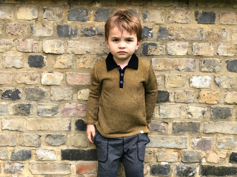 boy standing against brick wall wearing gold retro polo