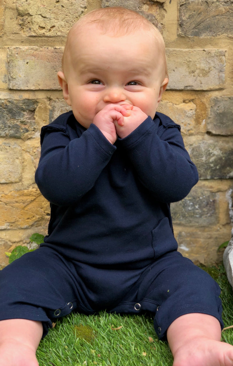 baby boy sat on grass wearing navy loose fit romper