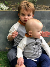 baby boy and older brother sat on grass wearing raglan tee