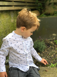 boy sat on wall touching a snail, wearing white shirt with navy spots