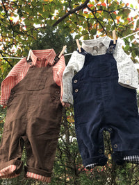 front image of brown corduroy overalls for baby boy hanging on clothes line with woven onesie