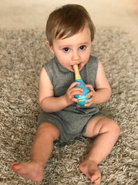 baby boy holding a rattle wearing grey sleeveless short legged romper