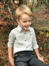 image of boy wearing long sleeved cotton grey woven shirt with navy spots all over