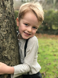 image of boy hiding behind a tree wearing long sleeved Henley tee with ecru and grey stripes and pocket