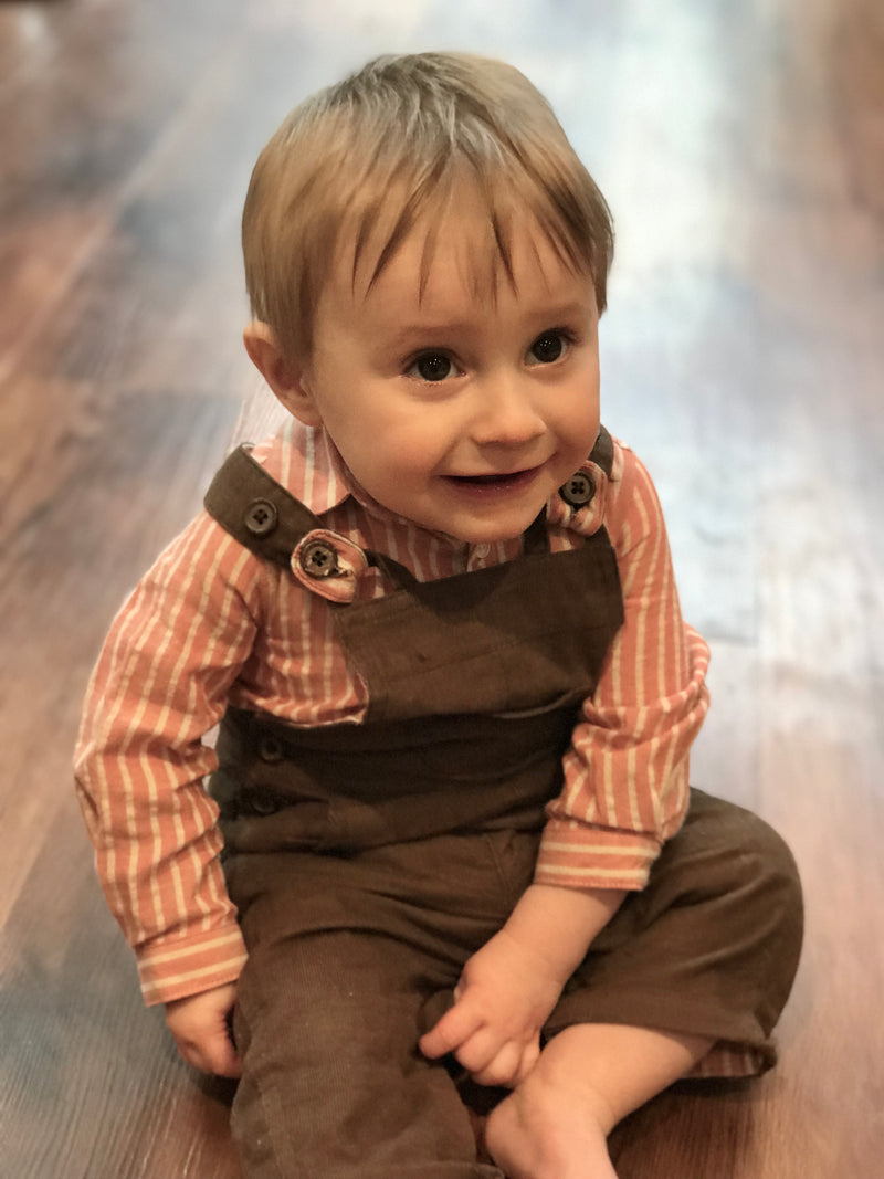 image of baby boy wearing brown corduroy overalls and orange woven onesie