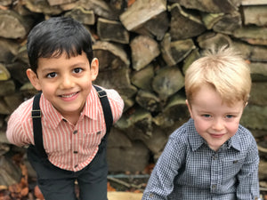 image of two boys, one wearing orange striped cotton shirt and black pants with suspenders, the other wearing a navy plaid shirt