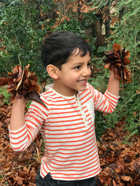 boy throwing leaves and wearing slub cotton orange and cream striped Henley tee