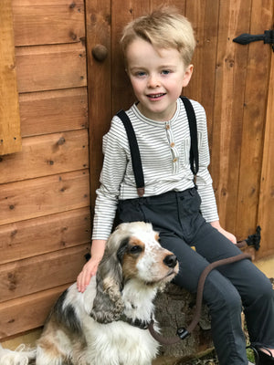 boy sat with Henry the dog wearing long sleeved Henley tee with ecru and grey stripes and pocket and back pants with suspenders