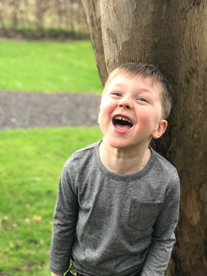 image of boy laughing wearing long sleeved black striped tee with pocket