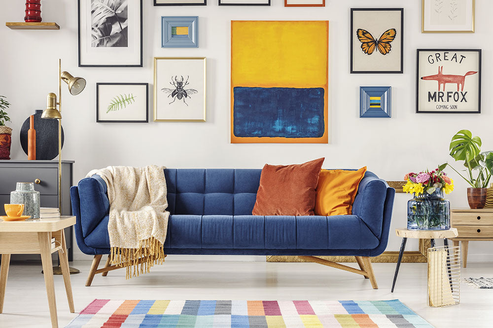 Blue sofa decorated with saffron and orange complementary throws