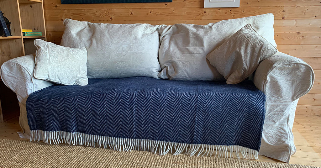 Navy Herringbone Blanket Covering Scuff Marks around the base of a sofa