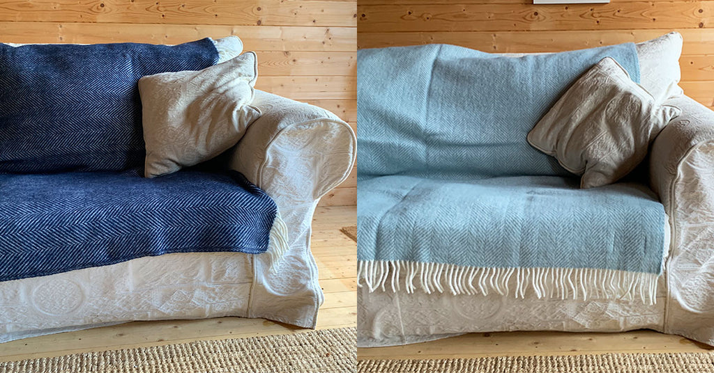 Duck Egg and Navy Herringbone Wool Blanket Covering the seat cushions on an old white sofa