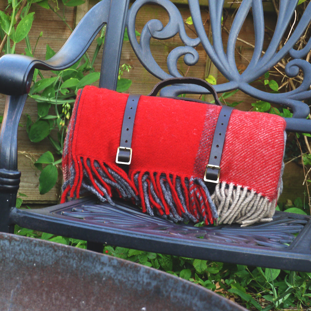 Red and grey check wool picnic blanket with waterproof backing and leather straps