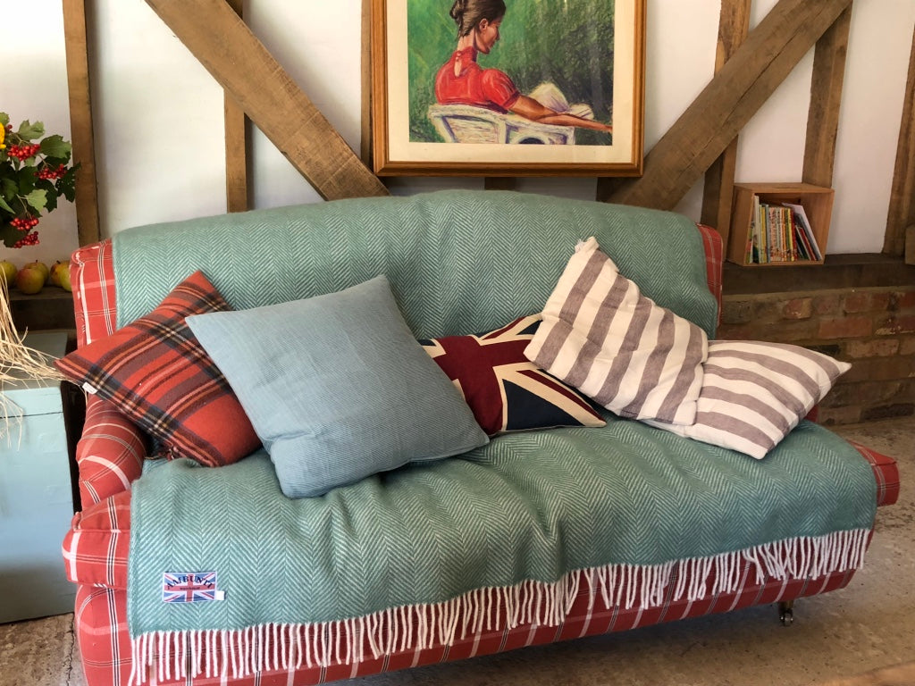 Green wool herringbone blanket being used to style a sofa