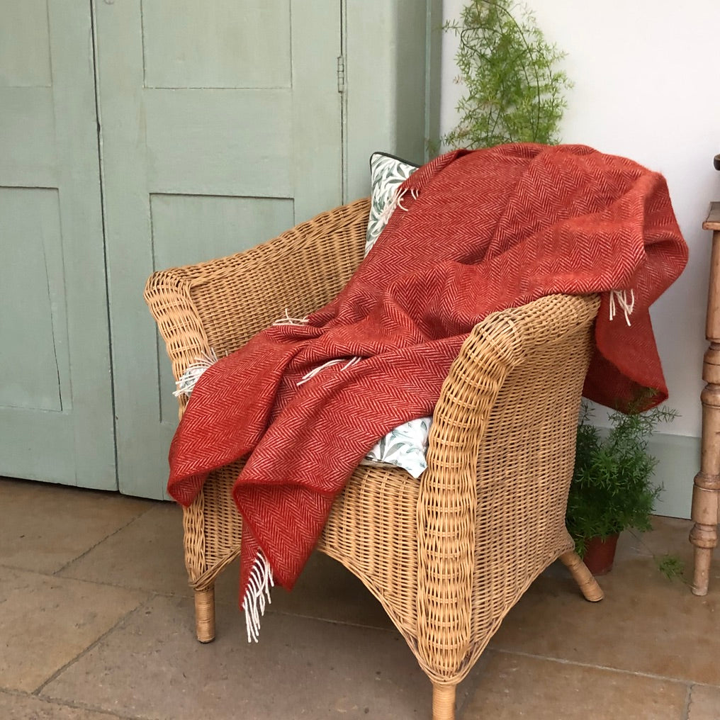 Style idea using an orange wool herringbone blanket thrown over a conservatory chair