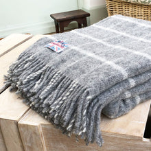 grey blanket folded up on a coffee table