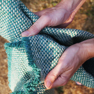 Close up showing the quality of the wool in the recycled crosshatch jade green throw.
