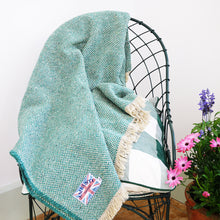 Recycled jade green wool throw draped over the back of a chair in the conservatory.