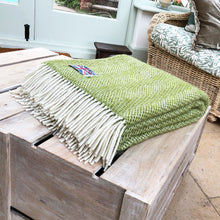 kiwi green beehive wool throw folded up on a coffee table