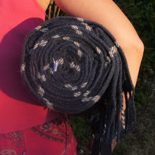 Navy blue and white waterproof wool picnic blanket rolled up and being carried by a young lady.