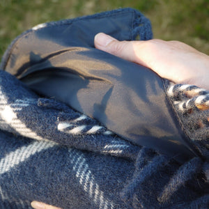 Close up of the navy blue and white waterproof wool picnic blanket shoing its equisite quality.