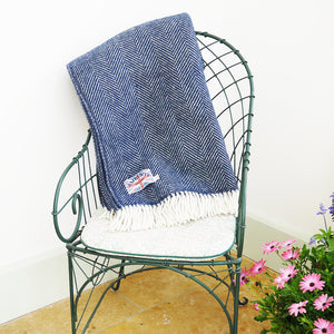 dark blue herringbone throw folded over the back of an iron chair