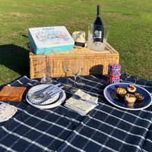 Navy blue wool picnic blanket spread out in a field