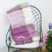 Lilac and cream wool block check blanket folded up on a chair in the conservatory.