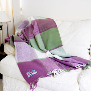 Lilac and cream wool block check throw draped on a sofa.